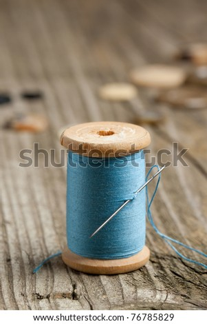 Spool of blue thread and needle on old wooden table - stock photo