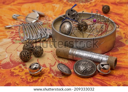 spool of thread,button,fabric and other items for needlework - stock photo