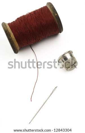 spool of thread, needle and a thimble on white