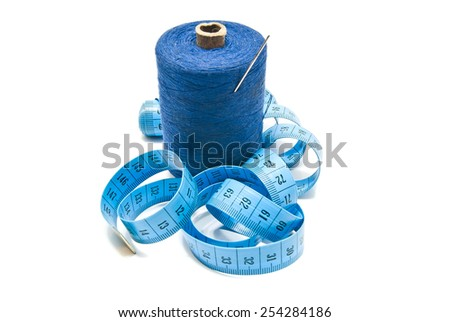 spool of thread with needle and meter on white - stock photo
