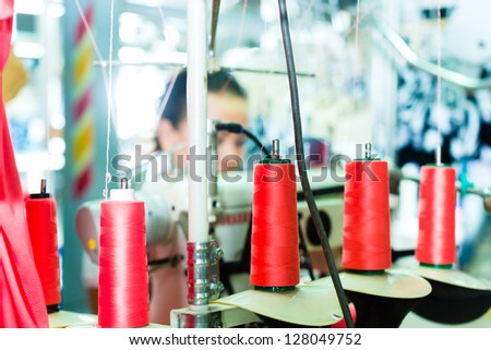 Spools of an industrial sewing machine in a factory, in the background working a seamstress - stock photo
