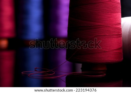 Spools of colored cotton thread, ordered composition, warm colors, red spool in the foreground with the red wire coiled in the form of  black table reflection, sprockets into the background blurred - stock photo