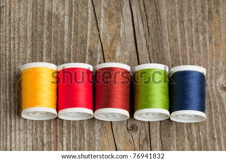 Spools of colorful threads on old wooden table - stock photo
