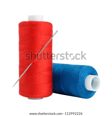 Spools of thread and needle isolated on white background - stock photo