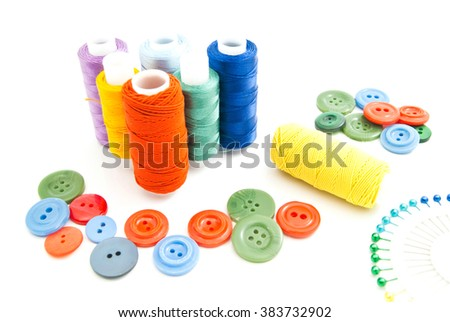 spools of thread, pins and buttons on white