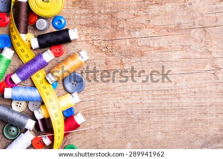 Spools of threads and buttons on old wooden table - stock photo