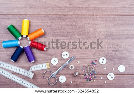 Spools with different colors of thread, scissors, buttons, sewing supplies, measuring tape and accessories for needlework on wooden background. Set for needlework top view - stock photo
