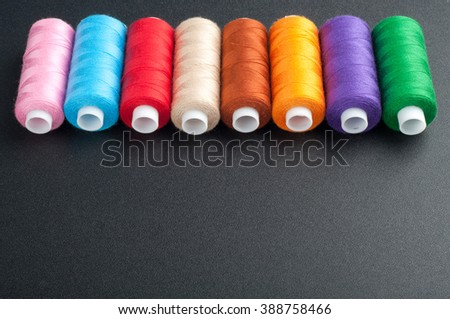 Spools with various colors of thread on dark background. Sewing background with copy space - stock photo