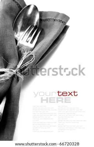 Spoon and fork in textile napkin over white with sample text - stock photo