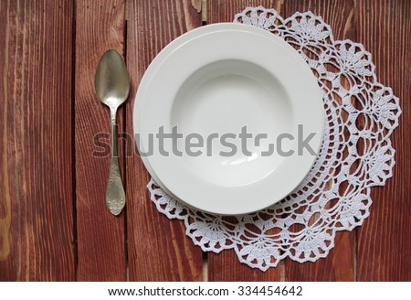 spoon and set of dining plates on lacy napkin.Rustic wooden table background.