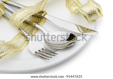 Spoon, fork and a knife tied up celebratory ribbon. Lie on a plate - stock photo