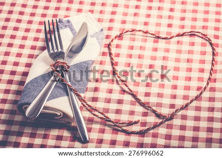 Spoon, fork and a knife with napkin on dinner table with heart rope shape. Vintage filter.