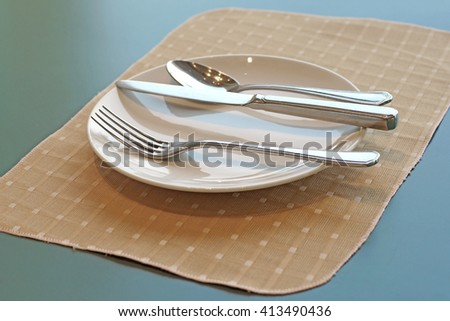 spoon fork and knife on empty white plate