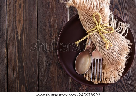 spoon, fork and knife on plate and on a table - stock photo
