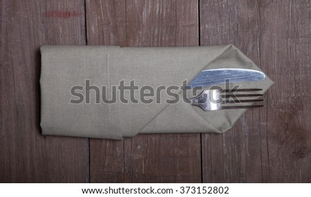 Spoon in napkin on wooden background. - stock photo