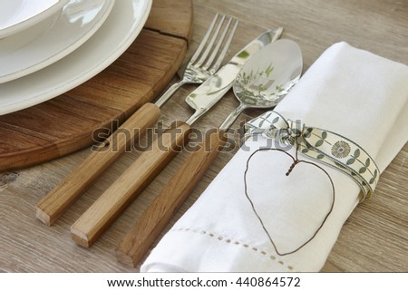 Spoon knife fork and dishware over a rustic table. Horizontal - stock photo