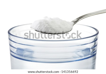 Spoon of baking soda over glass of water - stock photo