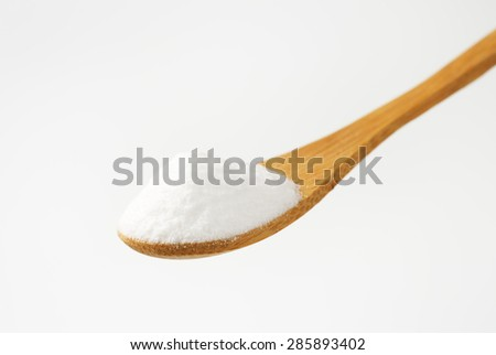 spoon of cooking soda on white background - stock photo