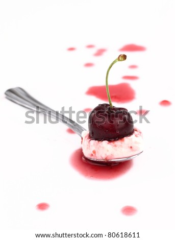 Spoon of cream with syrup and cherry on top - stock photo