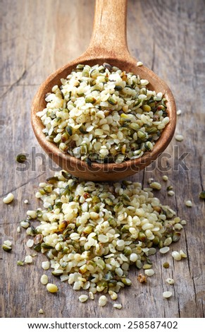 spoon of hemp seeds on old wooden table background - stock photo