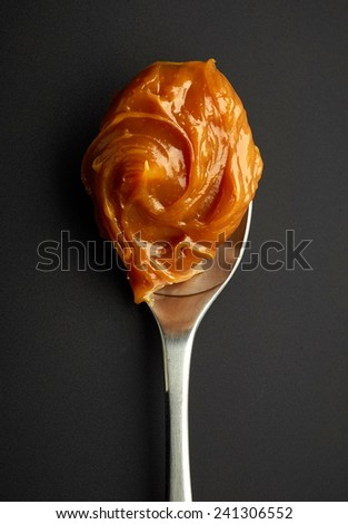 Spoon of melted caramel cream on black plastic background - stock photo