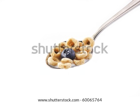 Spoon of oat cereal and a blue berry with milk