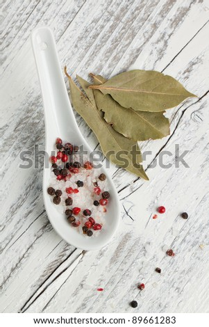 Spoon of salt and pepper with bay-leaf on white wooden table - stock photo