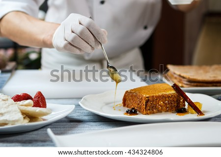 Spoon pouring honey on plate. Plate with piece of cake. Delicious honey cake with decoration. Creating new design for dessert. - stock photo