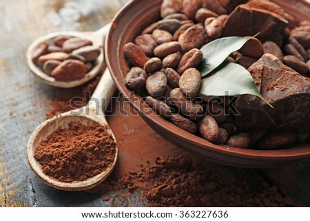 Spoon with aromatic cocoa powder and green leaf, close up - stock photo