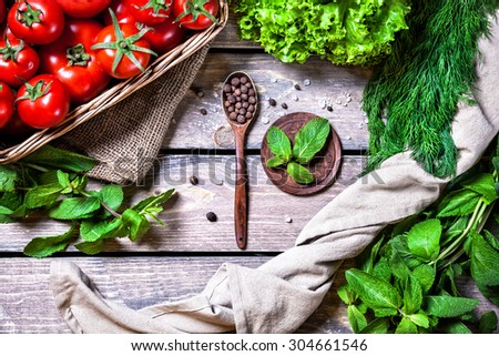 Spoon with black pepper, tomato, herbs and green salad on the wooden table in the kitchen - stock photo