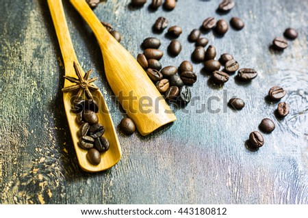 Spoon with coffee beans and spices like anise star on rustic wooden background - stock photo