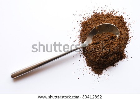 Spoon with coffee on white background - stock photo