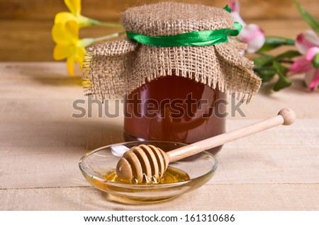 Spoon with honey in a transparent saucer on a wooden table - stock photo