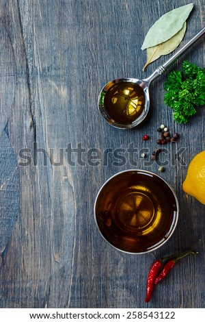 Spoon with Olive Oil and spices on wooden table. Top view. - stock photo