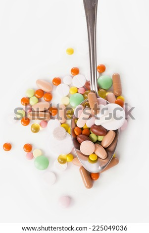 spoon with pills isolated on white background - stock photo