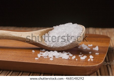 Spoon with sea salt on cutting board.