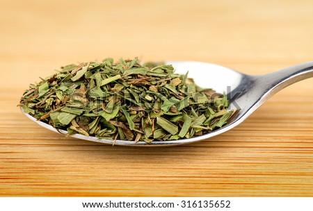 Spoonful of aromatic tarragon herb - stock photo