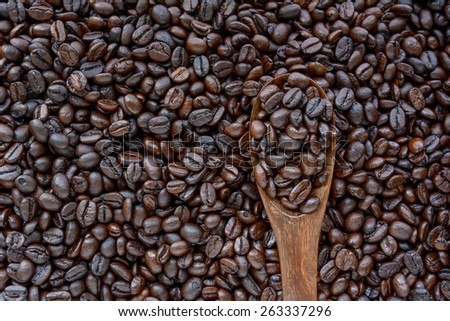 Spoonful of coffee beans on coffee bean heap - soft focus - stock photo