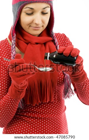 Spoonful of cough syrup being filled by young woman in winter cap and mittens - stock photo