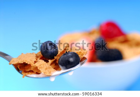 Spoonful of crispy bran flakes with fruit with bowl of cereal in the background - stock photo