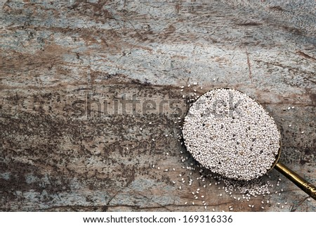 Spoonful of white chia seeds, over grunge timber background. - stock photo