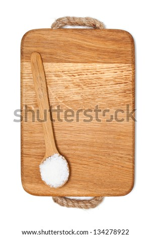 spoonfull of salt on wooden board and empty space for your text - stock photo