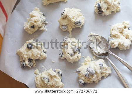 Spooning out batter into biscuit shapes on parchment paper - stock photo