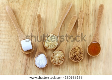 Spoons of different types of sugar, sugar cube, granulated white sugar, granulated light brown sugar, brown sugar crystals, soften brown sugar, honey on the wooden background - stock photo