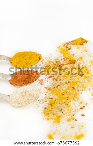 Spoons with seasoning and scattered around. Vertical. White background.