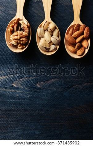 Spoons with walnuts, pistachios and almonds, on grey wooden background - stock photo