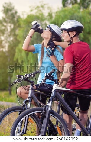 Sport and cycling Concept: Young Caucasian Cyclist Resting Together Outdoors. Having Water Break and Relaxing.Vertical Image Composition - stock photo
