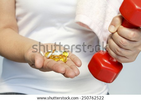 sport and diet concept - woman hand with vitamins and medication - stock photo