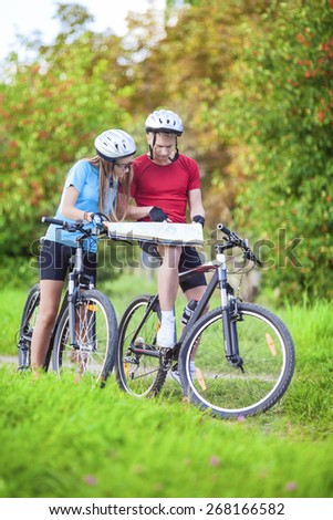 Sport and Fitness Concept. Happy caucasian Couple of Cyclists With Location Map Outdoors. Vertical Image Composition - stock photo