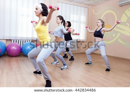 Sport and Fitness Concepts. Four Professional Sportswomen Having Trunk Bending Exercises with Barbells. Training In Sport Class. Horizontal Image - stock photo